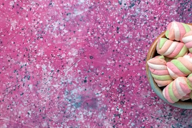 Oben nähere ansicht süße farbige marshmallows wenig gebildet im runden topf auf rosa schreibtisch.