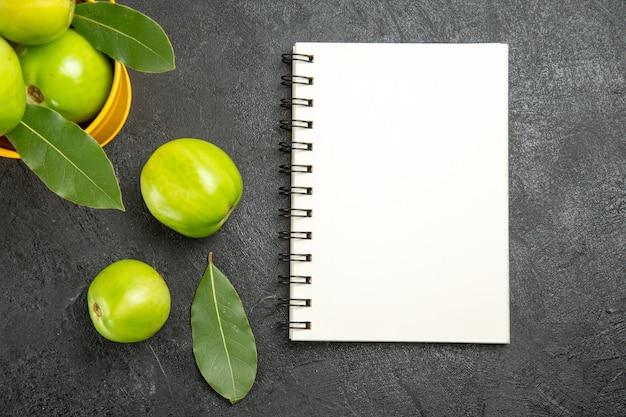 Oben nahansicht eimer mit grünen tomaten und lorbeer hinterlässt ein notizbuch und tomaten auf dunklem tisch
