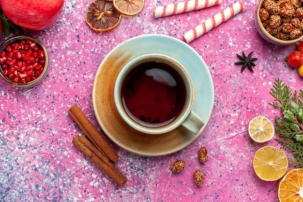 Oben nahansicht frischer granatapfel mit grünen blättern und tasse tee auf rosa wandfrucht frische milde herbstbaumpflanzenfarbe