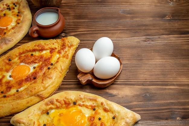 Oben nahansicht gebackene eierbrote frisch aus dem ofen auf holzoberfläche teig eierbrötchen frühstücksbrot