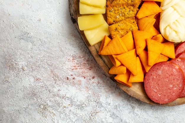 Oben nahansicht verschiedene snacks cips würstchen käse und frische trauben auf weißraum