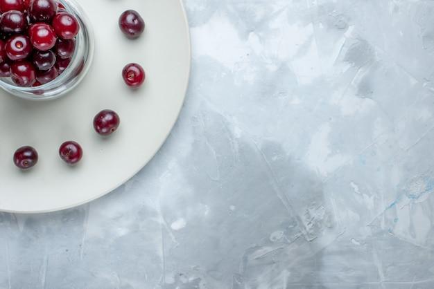 Oben nahansicht von frischen sauerkirschen in platte auf hellem schreibtisch, fruchtsauerbeeren-vitaminsommer