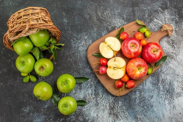 Oben nahaufnahme ansicht äpfel korb von grünen äpfeln mit blättern brett mit roten äpfeln kirschen