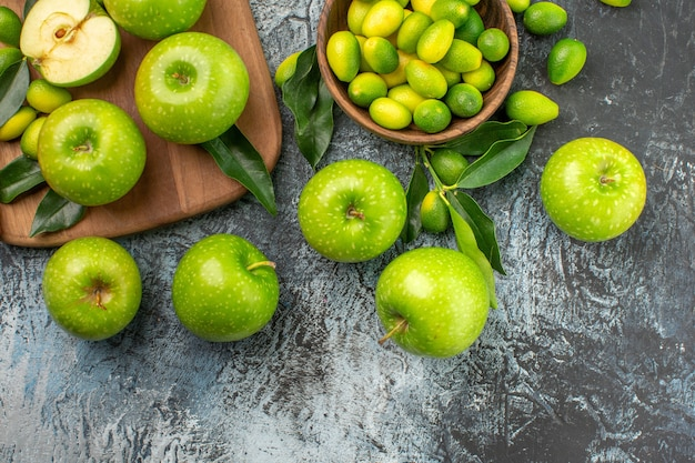Oben nahaufnahme ansicht äpfel schüssel zitrusfrüchte brett des appetitlichen grünen äpfel messers