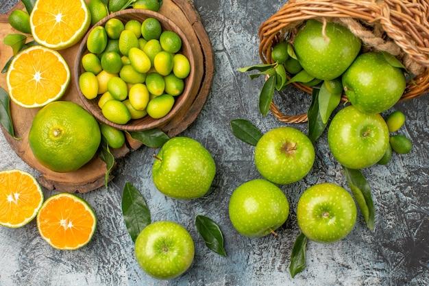 Oben nahaufnahme ansicht äpfel zitrusfrüchte auf dem brett grüne äpfel mit blättern im korb