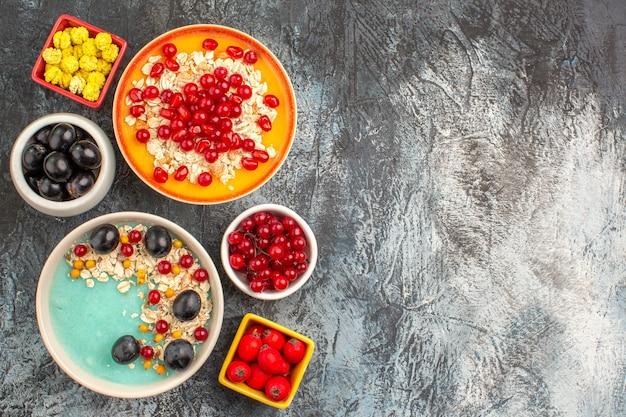 Oben nahaufnahme ansicht beeren schwarze trauben kirschen rote johannisbeeren haferflocken granatapfel gelbe bonbons