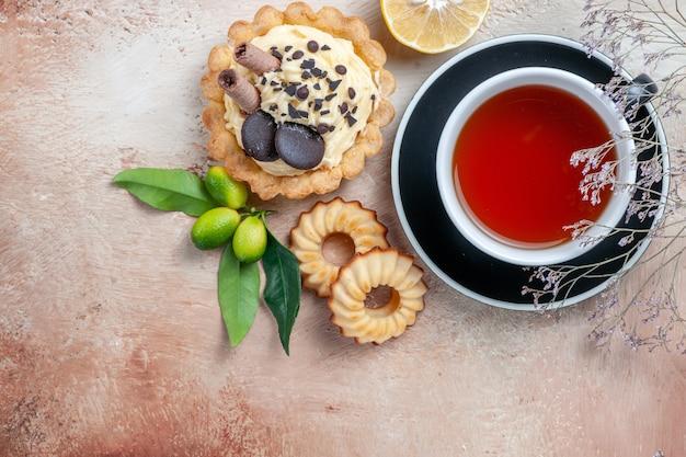 Oben nahaufnahme ansicht eine tasse tee cupcake kekse eine tasse tee zitrusfrüchte