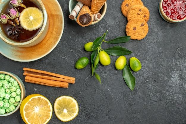 Oben nahaufnahme ansicht eine tasse tee kekse eine tasse tee bonbons marmelade zitrone zimt zitrusfrüchte