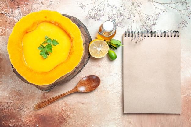 Oben nahaufnahme ansicht einer suppe kürbissuppe mit kräutern auf dem brettlöffel öl zitronencreme notizbuch