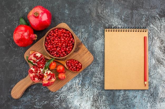 Oben nahaufnahme ansicht früchte notizbuch bleistift das brett mit granatapfel löffel kirschen