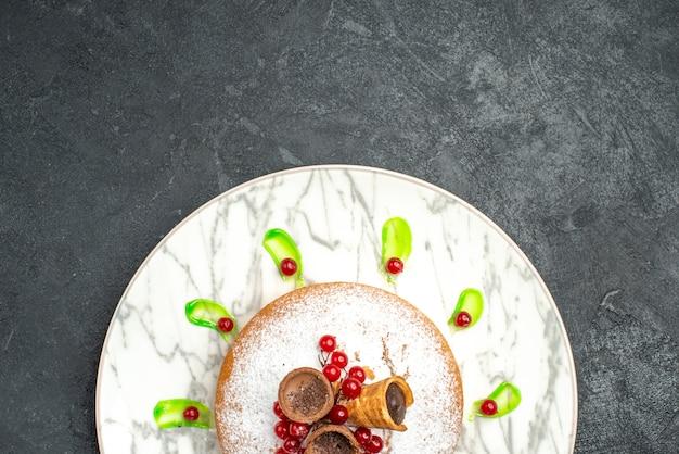Oben nahaufnahme eines kuchengrauen tellers eines kuchens mit puderzucker der grünen soße beeren