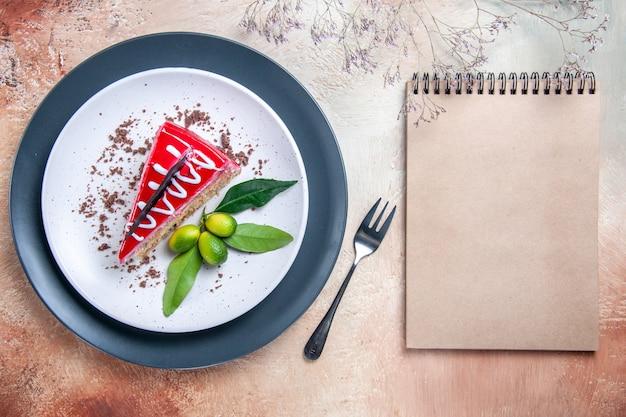Oben nahaufnahme eines kuchentellers kuchen mit schokoladensaucen zitrusfrüchten gabel creme notizbuch
