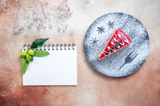 Oben nahaufnahme eines kuchentellers von kuchen-notizbuch-zitrusfrüchten