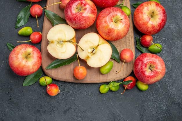 Oben nahaufnahmefrüchte früchte zitrusfrüchte neben den äpfeln und kirschen auf dem brett
