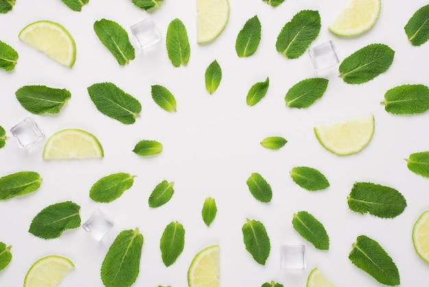 Oben oben foto von minzblättern, eiswürfeln und limettenscheiben, die in kreisen liegen, mit leerer mitte isoliert auf weißem hintergrund