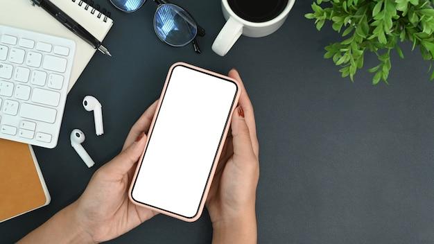 Oben sehen frau, die ein smartphone mit weißem bildschirm über ihrem schreibtisch hält.