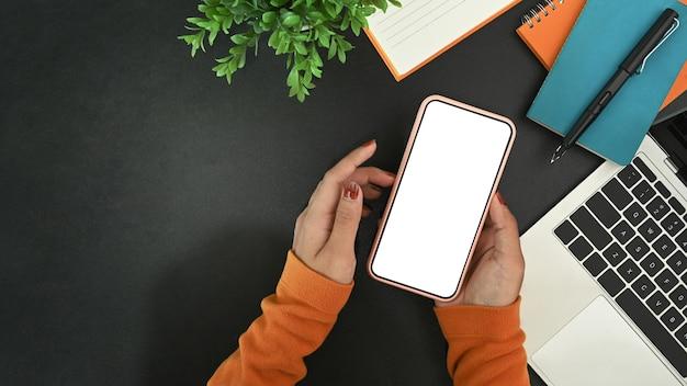 Oben sehen sie eine stilvolle frau, die ein smartphone mit weißem bildschirm auf einem modernen arbeitsplatz hält.