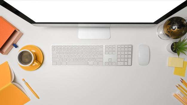 Oben sehen sie einen stilvollen arbeitsplatz mit computer, kaffeetasse und notebook auf weißem schreibtisch.