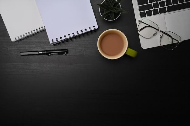 Oben sehen sie laptop-computer, notebook und tasse kaffee auf schwarzem tisch.