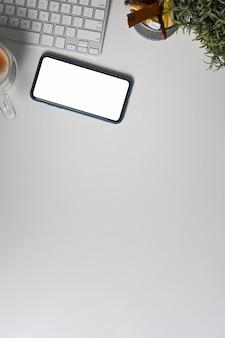 Oben sehen sie smartphone mit leerem bildschirm auf weißem schreibtisch.