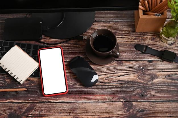 Oben sehen sie smartphone mit weißem bildschirm, notebook, smartwatch und kaffeetasse auf holztisch.