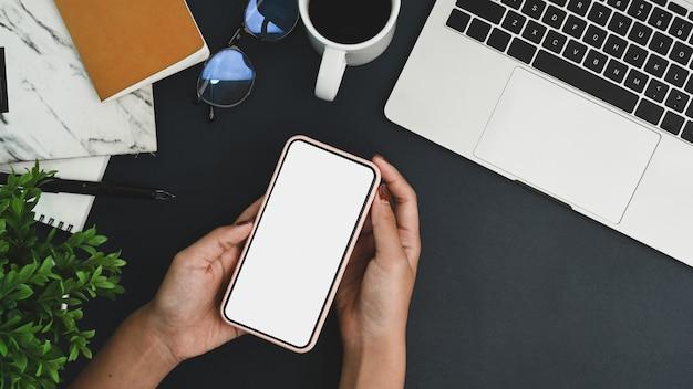 Oben sehen weibliche hände, die ein smartphone mit weißem bildschirm über ihrem arbeitsplatz halten.