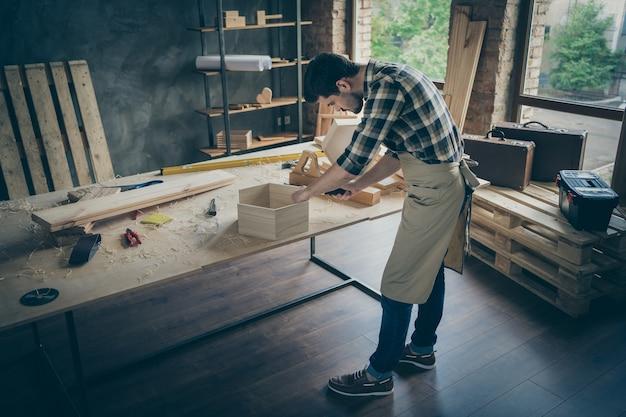 Oben über dem hohen winkel in voller länge fokussierte professionelle arbeiter verwenden schraubendreher fix regal auf tischplatte in der garage des hauses