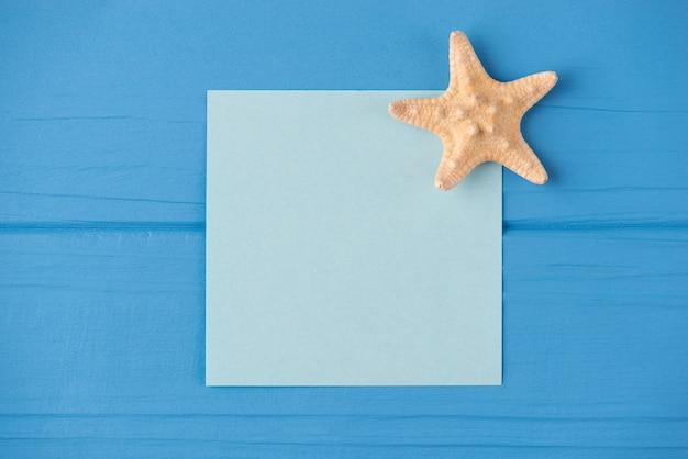 Oben über der draufsicht nahaufnahme einer leeren notiz mit einem kleinen seestern einzeln auf blauem holzhintergrund mit exemplar