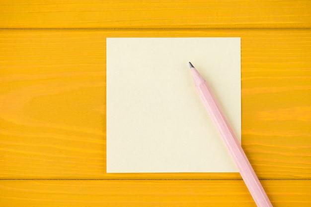 Oben über der draufsicht, nahaufnahme einer leeren notiz und eines bleistifts, isoliert auf gelbem holzhintergrund mit exemplar