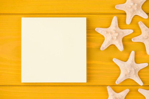 Oben über der draufsicht, nahaufnahme von seesternen und leeren haftnotizen einzeln auf gelbem holzhintergrund mit exemplar