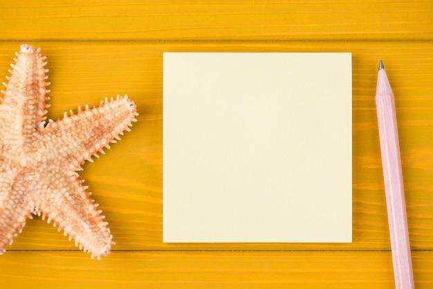 Oben über der draufsicht, nahaufnahme, zugeschnittenes foto von seestern, leere notiz und bleistift, isoliert auf gelbem holzhintergrund mit kopienraum