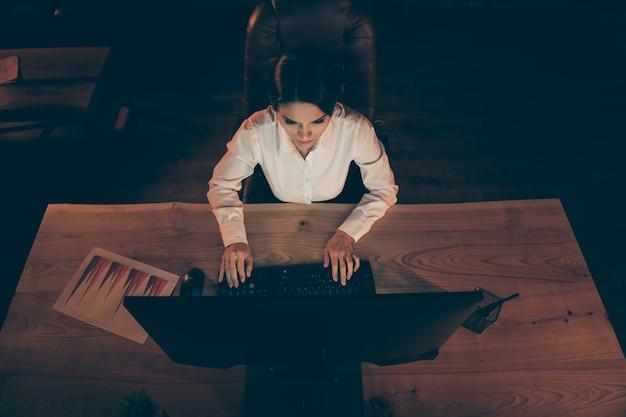 Oben über der high angle view von ihr hat sie eine schöne, attraktive, fokussierte geschäftsfrau, wirtschaftsprüferin, fleißige eingabe, die einen plan für einen finanzmanagement-strategiebericht in der nacht am dunklen arbeitsplatz erstellt
