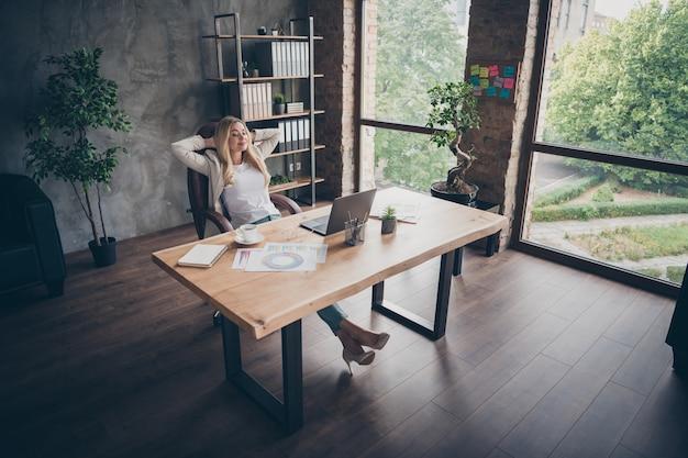 Oben über high angle view unternehmer, der sich in hochhackigen schuhen mit geschlossenen augen ausruht und mit geschlossenen augen zufrieden über ihre ergebnisse ist