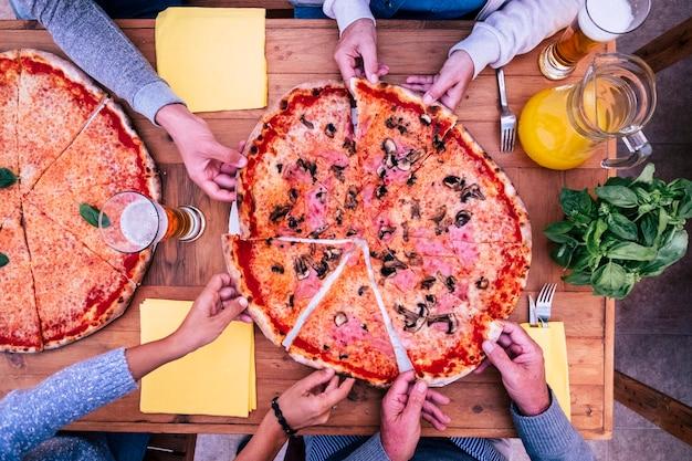 Oben und draufsicht auf zwei große pizzen mit vielen händen, die ein stück davon nehmen - holztisch - abendessen in familie oder freunden