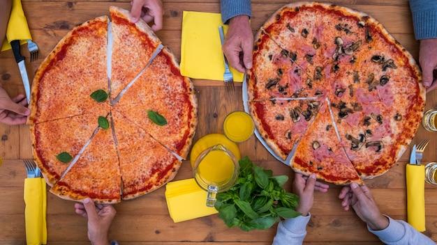 Oben und draufsicht auf zwei große pizzen oder bekannte pizzen, die zu hause auf dem holztisch gekocht werden - familie, die zusammen isst und trinkt