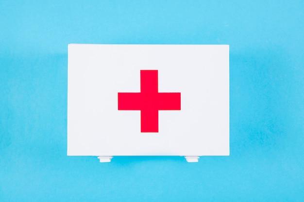 Obenliegende ansicht der ausrüstung der ersten hilfe mit medizinischem zeichen auf blauem hintergrund