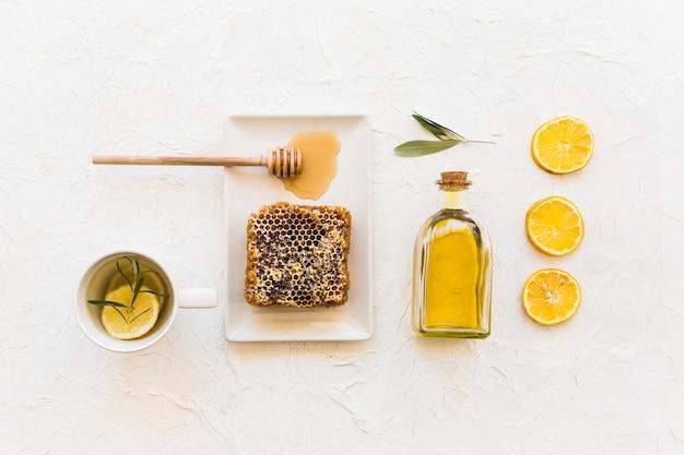 Obenliegende ansicht der bienenwabe mit olivenöl- und zitronenscheibe auf weißer tapete