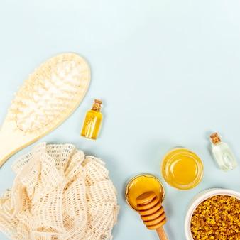 Obenliegende ansicht der bürste; flasche mit ätherischem öl; honigglas; bienenpollen und luffa