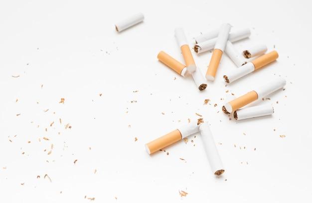 Obenliegende ansicht der defekten zigarette und des tabaks gegen weißen hintergrund