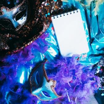 Obenliegende ansicht der dekorativen augenmaske und der karnevalsgegenstände mit leerem gewundenem notizblock
