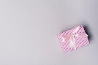 Obenliegende Ansicht der eingewickelten Geschenkbox mit rosa Bogen auf grauem Hintergrund