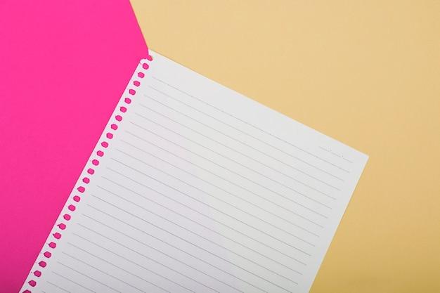 Obenliegende ansicht der einzelnen seite auf rosa und goldenem hintergrund