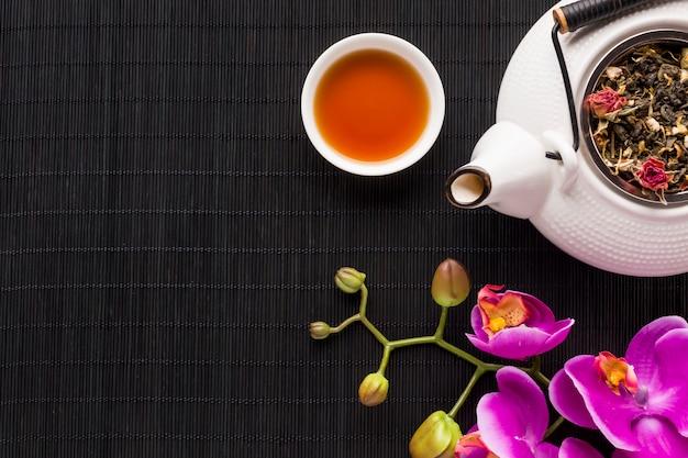 Obenliegende ansicht der empfindlichen rosa orchideenblume und des trockenen teekrauts mit teekanne