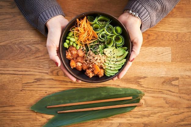 Obenliegende ansicht der frau traditionelle hawaiische tellerstoßschüssel in den händen auf hölzernem halten. hawaiianische und japanische küche. gesundes essen.