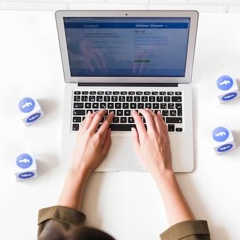 Obenliegende ansicht der frauenanmeldung in facebook auf laptop auf weißer tabelle