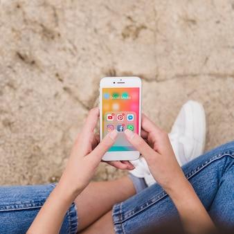 Obenliegende ansicht der frauenhand unter verwendung des mobiltelefons mit mitteilungen auf schirm