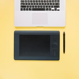 Obenliegende ansicht der grafischen digitalen tablette und des laptops auf gelber oberfläche