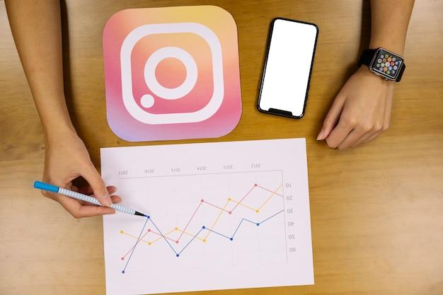 Obenliegende ansicht der hand das instagram diagramm analysierend