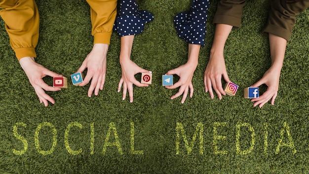 Obenliegende ansicht der hand der frau, die sozialnetz-app-symbolblöcke auf rasen hält