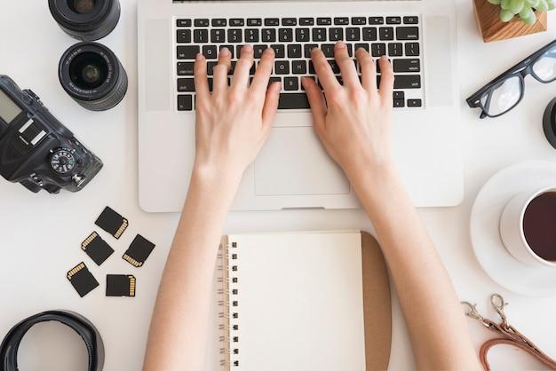 Obenliegende ansicht der hand der person, die auf laptoptastatur mit kamerazubehör und persönlichem zubehör und tee schreibt